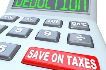18138261 - a calculator red button with the words save on taxes and the term deductions on the display, illustrating tax savings in the form of loopholes, losses and exemptions
